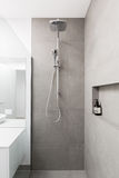 Le luxe a entièrement couvert de tuiles la douche avec la tête de pluie et la douche tenue dans la main image stock