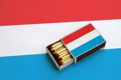 Le Luxembourg diminuent est montré dans une boîte d'allumettes ouverte, qui est remplie de matchs et se trouve sur un grand drape images libres de droits