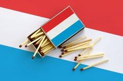 Le Luxembourg diminuent est montré sur une boîte d'allumettes ouverte, de laquelle plusieurs matchs tombent et des mensonges sur  image libre de droits