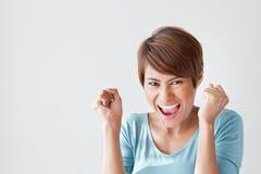 Le lycklig, positiv upphetsad kvinna på vanlig bakgrund Arkivbild