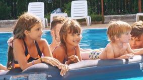 Le lyckliga barn på en flöte i en simbassäng arkivfilmer