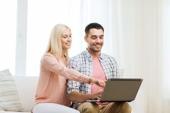 Le lyckliga par med bärbar datordatoren hemma Fotografering för Bildbyråer