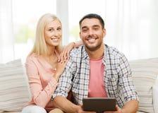 Le lyckliga par med minnestavlaPC hemma Arkivbild