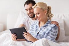 Le lyckliga par med minnestavlaPC i säng hemma Arkivfoto