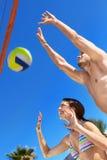 Le lyckliga par som spelar volleyboll Arkivbilder