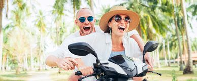 Le lyckliga parhandelsresande som rider mopeden under deras tropiska semester under palmträd royaltyfria bilder