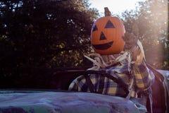 Le lyckligt och att välkomna, rolig vänlig pumpahuvudfågelskrämma som kör en gammal lastbil till ett halloween skördparti fotografering för bildbyråer