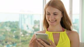 Le lyckligt sammanträde för ung kvinna på balkong Genom att använda hennes mobiltelefon och att bläddra och att läsa nyheterna stock video
