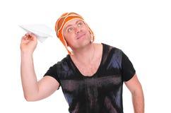 Le mâle adulte dans un ` s d'enfants a tricoté le pilote de chapeau jouant avec un avion de papier L'homme a laissé un avion de p Photos libres de droits