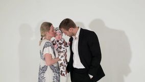 Le mâle aux yeux bleus mûr dans le costume se tient à côté de la femme qui tient le bébé dans des mains clips vidéos
