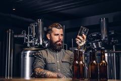 Le mâle avec la barbe et les cheveux élégants tient la pinte de bière de métier se reposant au compteur de barre dans la brasseri photos stock