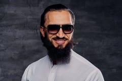 Le mâle barbu avec de longs cheveux s'est habillé dans une chemise blanche et des lunettes de soleil Photos libres de droits