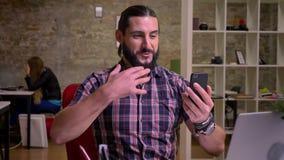 Le mâle barbu caucasien heureux mignon a l'appel visuel et montre son T-shirt occasionnel tout en se reposant sur le lieu de trav banque de vidéos
