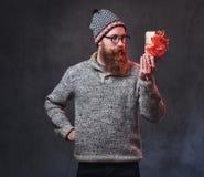 Le mâle barbu tient des cadeaux de Noël images libres de droits