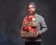 Le mâle barbu tient des cadeaux de Noël photo stock