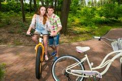 Le mâle beau enseigne son amie montant une bicyclette en parc Photos libres de droits