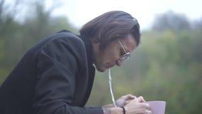 Le mâle boit la mauvaise eau et la crache type beau dans un costume et des lunettes de soleil banque de vidéos