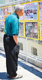 Le mâle chinois aîné affiche des newpapers Photos libres de droits