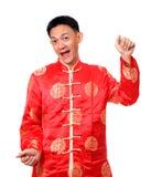 Le mâle chinois heureux dans le cheongsam remet tenir les paquets rouges/ANG photo stock