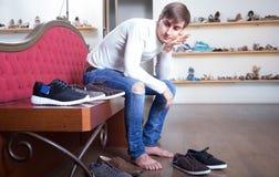 Le mâle choisit des chaussures d'hiver dans un magasin de chaussures image stock