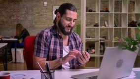 Le mâle créatif impressionnant de cauasin avec de longs cheveux noirs de la barbe NAD frappe à toute volée son téléphone tout en  banque de vidéos