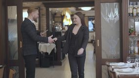 Le mâle d'affaires et les associés féminins se réunissent dans le restaurant Les gens se serrant la main Madame dans venir élégan clips vidéos