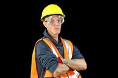 Le mâle de travailleur de la construction dans le chapeau de sécurité jaune, gilet orange, gants rouges, google et étant prêt pou Photographie stock libre de droits
