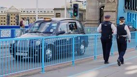 Le mâle et les policiers féminins patrouillent le pont de tour photo libre de droits