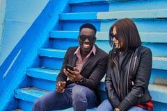 Le mâle féminin et noir caucasien s'assied sur une étape et employer p futé Photos stock
