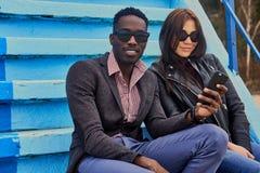 Le mâle féminin et noir caucasien s'assied sur une étape et employer p futé Images stock