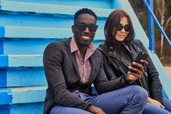 Le mâle féminin et noir caucasien s'assied sur une étape et employer p futé Photographie stock libre de droits
