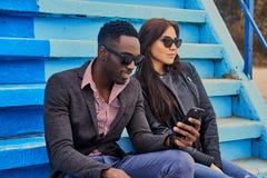 Le mâle féminin et noir caucasien s'assied sur une étape et employer p futé Images libres de droits