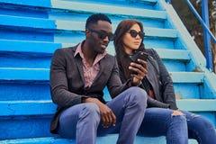 Le mâle féminin et noir caucasien s'assied sur une étape et employer p futé Image libre de droits