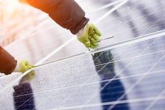 Le mâle installe les batteries solaires utilisant des outils par temps couvert de neige Images libres de droits