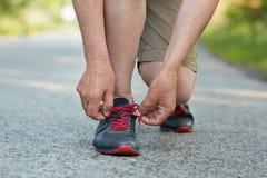 Le mâle méconnaissable a les jambes atheltic minces, dentelles noires et les chaussures de course rouges, se prépare au matin pul Image stock