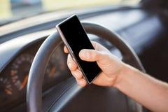 Le mâle méconnaissable tient le téléphone intelligent dans la voiture sur le fond de roue, écran vide de copie pour le texte de y photos libres de droits