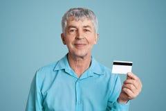 Le mâle mûr heureux avec l'expression gaie dans la chemise formelle, prises créditent la carte en plastique, heureuse d'obtenir l images libres de droits