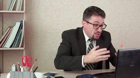 Le mâle mauvais de directeur de bureau avec une barbe et des verres Cris à l'ordinateur portatif banque de vidéos