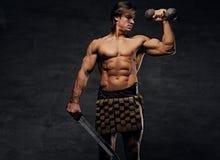 Le mâle musculaire sans chemise tient l'épée et les haltères photos libres de droits