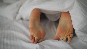 Le mâle paye dans le lit sous la couverture banque de vidéos
