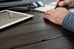Le mâle remet l'écriture dans un carnet sur la table de bureau Image libre de droits