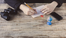 Le mâle remet le fond de café - ajournez les planches en bois, smartphone, nootbook, crayon, globe, jumelles, drapeau, but, réali Images stock