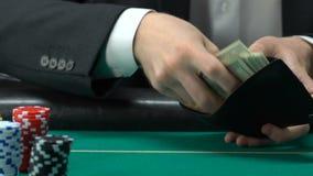 Le mâle satisfait de sa victoire, mettant des dollars emballent dans le portefeuille, jouant banque de vidéos