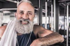 Le mâle supérieur positif sourit tout en se tenant au centre sportif Image libre de droits