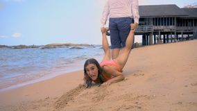 Le mâle tire une fille le long du bord de la mer, la fille résiste et veut se reposer plus loin, le concept de la fin des vacance photos libres de droits