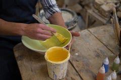 Le mâle traîne la main peignant une cuvette dans l'atelier de poterie photos stock