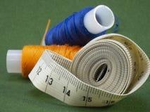Le mètre pour des tailleurs et les fils multicolores se trouvent sur un fond vert photo stock