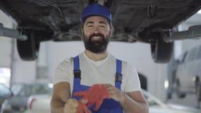 Le mécanicien adulte sort des gants se tenant sous la voiture et le sourire soulevés Homme barbu dans l'automobile de réparation  clips vidéos
