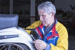 Le mécanicien ajuste un plat de motocyclette Image stock