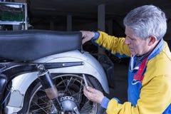 Le mécanicien ajuste un siège de motocyclette Image stock